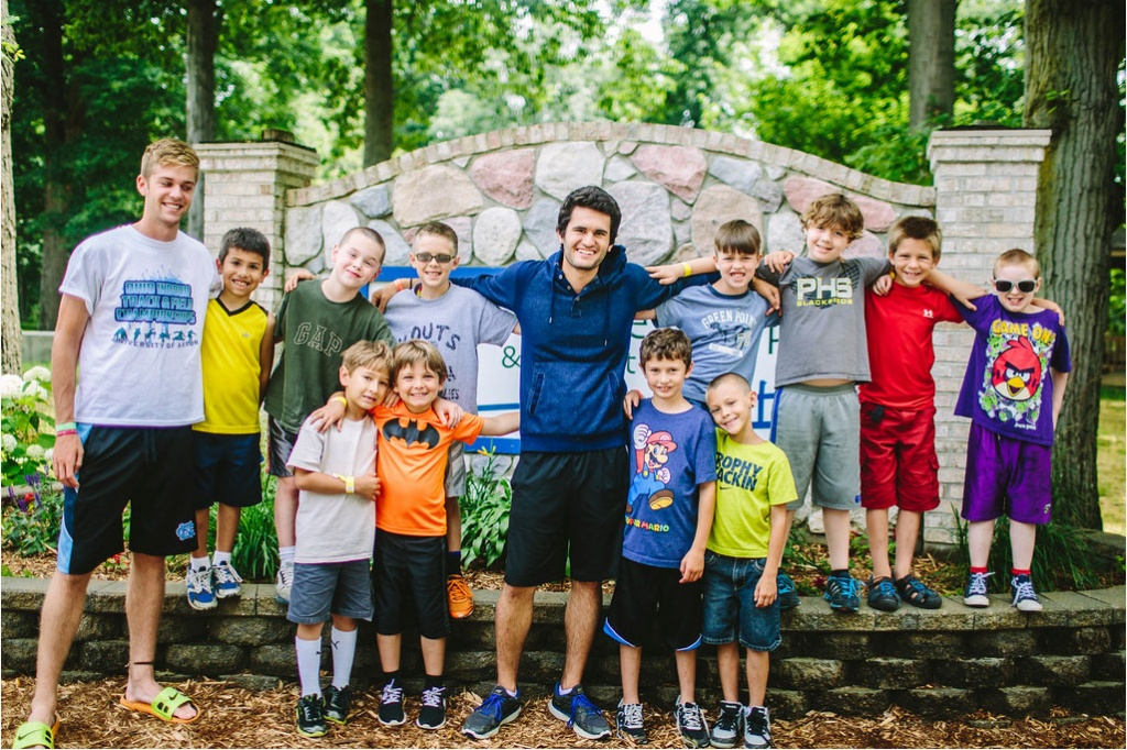 Brandon (far upper right in purple) and Tristan (lower right in neon green) pictured with their counselor Adam (middle in navy) and the rest for their cabin.